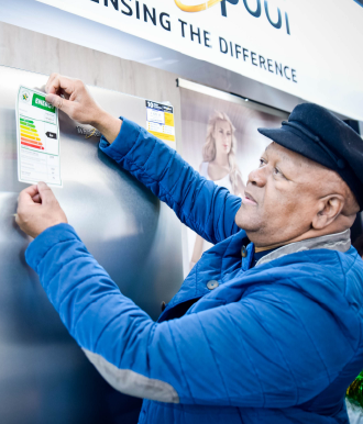 Minister of energy placing a energy saving label on a fridge